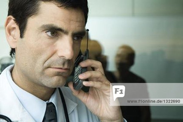 Doctor using cell phone  looking away