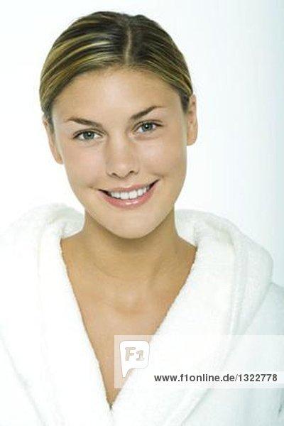 Junge Frau im Bademantel  lächelnd vor der Kamera  Portrait