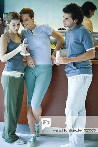Young adults in exercise clothing  taking break in health club cafeteria  looking at cell phone