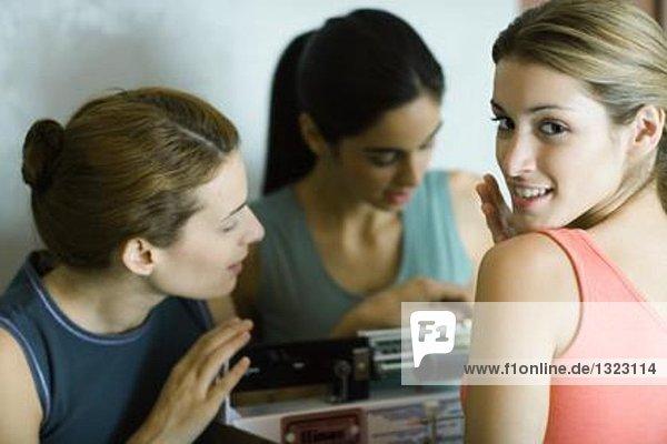 Frau steht auf der Waage  während Freunde das Gewicht betrachten.