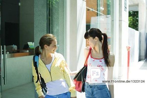 Two young women standing on sidewalk  looking at each other