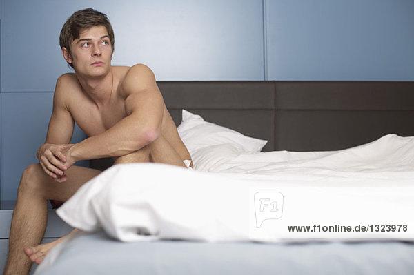 Junger nackter Mann sitzt im Bett - Erotik  fully_released
