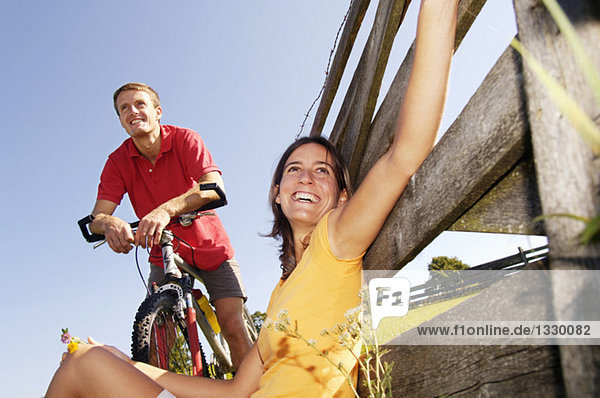 Couple having a rest  woman leaning on wooden railing