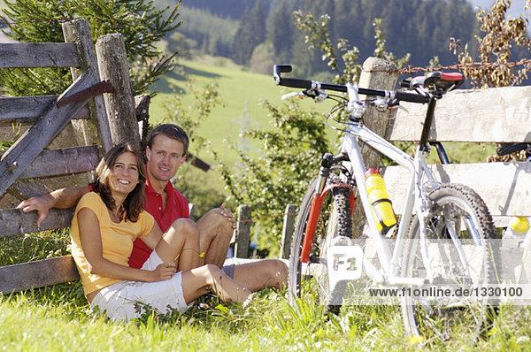Junges Paar auf der Wiese sitzend mit Mountainbike  auf Holzzaun gestützt