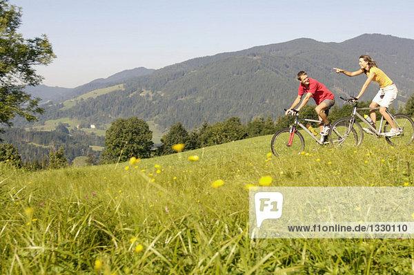 Junges Paar beim Mountainbiken auf der Wiese,  Seitenansicht,  Berge im Hintergrund