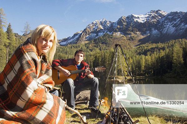 Junges Paar zelten am See  Mann spielt Gitarre