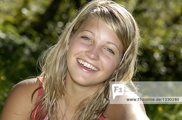 Teenage girl (16-17) sitting in meadow  smiling  close-up  portrait