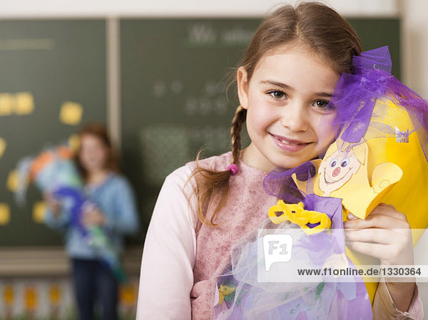 Girl (6-7) holding school cone  smiling  portrait  close-up