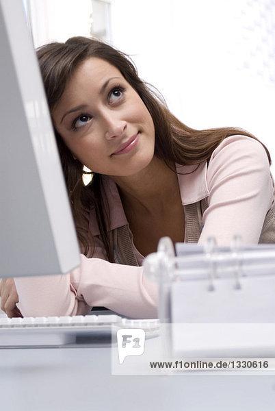 Junge Frau sitzt am Computer im Büro  schaut nach oben  lächelt