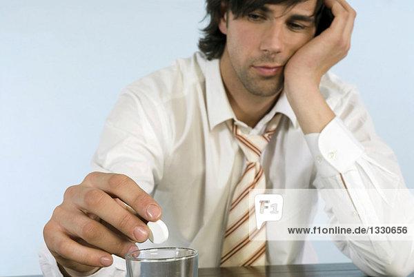 Geschäftsmann hält Pille  sitzt auf dem Schreibtisch mit einem Glas Wasser  Nahaufnahme