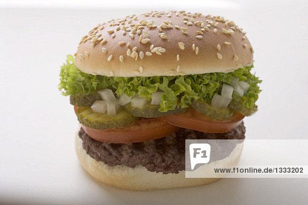 Hamburger mit Tomate  Gewürzgurke  Zwiebeln und Salat