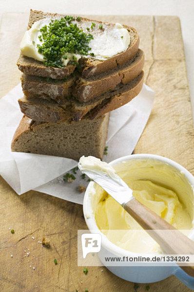 Mehrere Brotscheiben gestapelt mit Butter und Schnittlauch