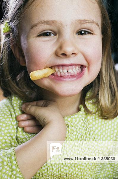 Kleines Mädchen isst ein Pommes Frites