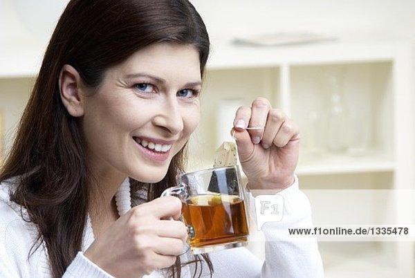 Frau hält Teetasse und Teebeutel in den Händen