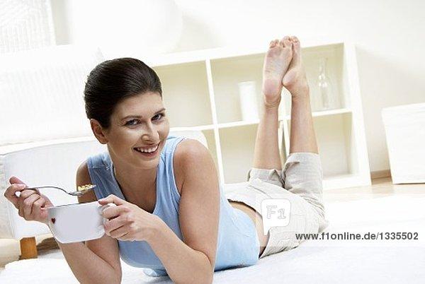 Frau isst Schokomüsli mit Milch