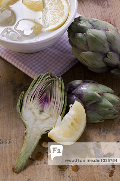 Frische Artischocken  Zitrone und Schale mit Zitronenwasser