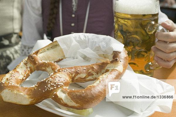 Frau mit Mass Bier und Brezel beim Oktoberfest