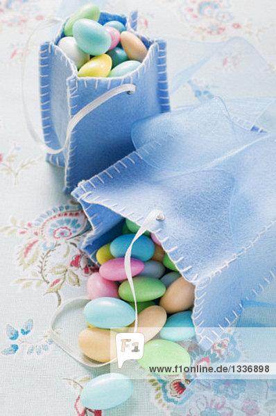 Mandeln mit Zuckerglasur in zwei blauen Stofftüten