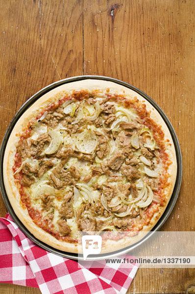 Thunfisch-Zwiebel-Pizza auf Holzuntergrund