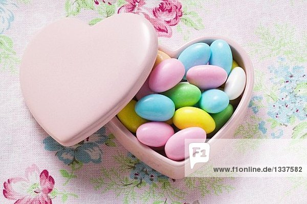 Coloured sugared almonds in pink heart-shaped dish 955425