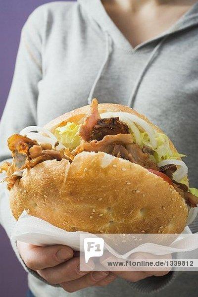 Frau hält Döner Kebab Sandwich