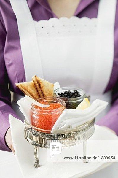 Zimmermädchen serviert Kaviar und Toast