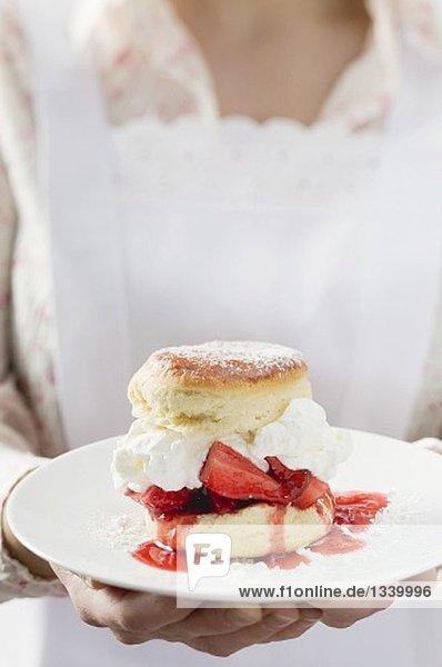 Zimmermädchen serviert Teller mit Strawberry Shortcake