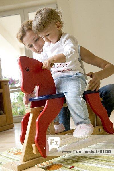 Baby Spiel mit um auf Schaukelpferd