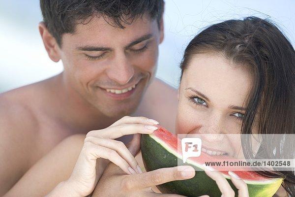 paar Essen Wassermelone am Strand