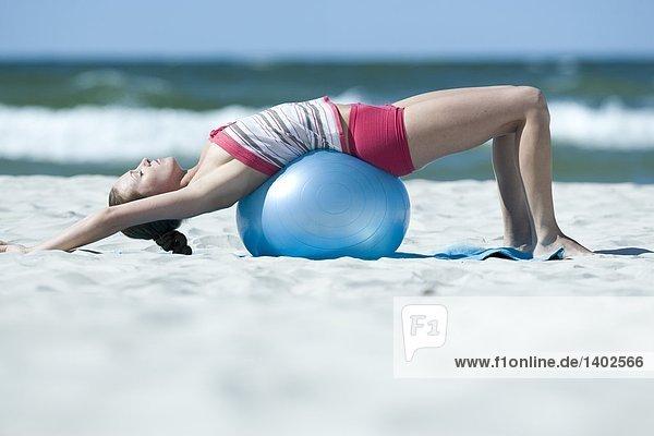 Frau beim training mit Ausbildung Ball am Strand