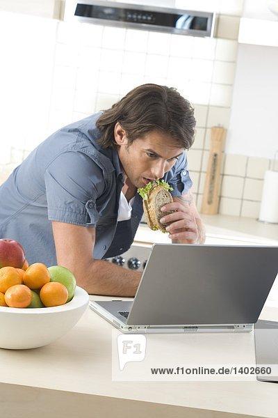 Man essen Frühstück und am Computer arbeiten