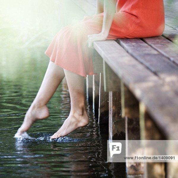 Junge Frau sitzend von einem Fluss
