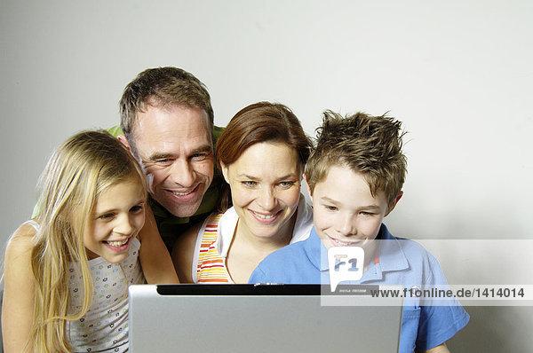 Familie schauen  Laptop und lächelnd
