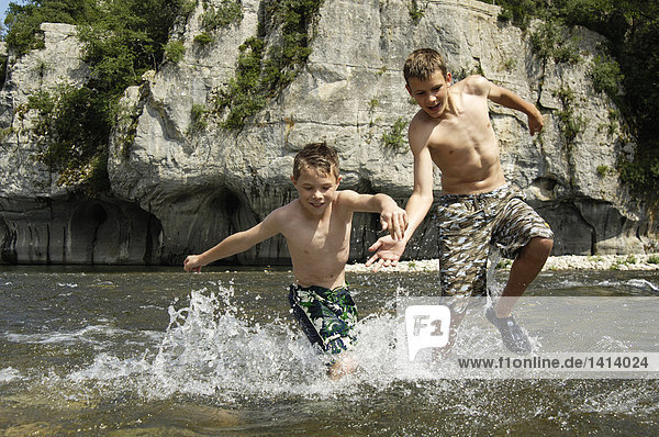 Two brothers running in river