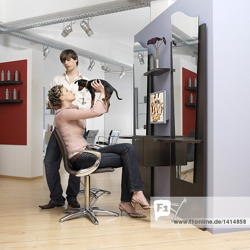 Junge Frau hält Hund beim Friseur