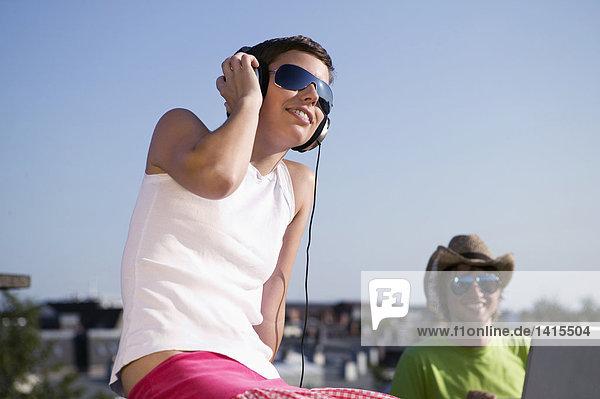 Junger Mann benutzt Laptop  während die Frau Musik hört.