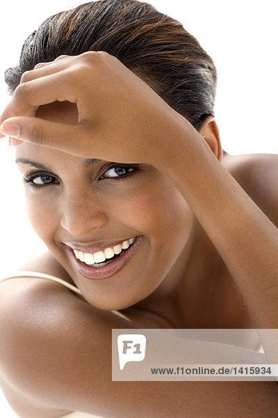 Porträt einer jungen lächelnden Frau  Hand auf der Stirn
