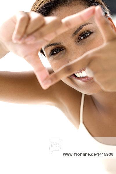 Porträt einer jungen lächelnden Frau  die mit den Fingern einen Rahmen macht.