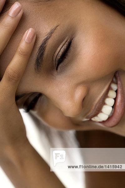 Porträt einer lächelnden Frau  Hand auf der Stirn