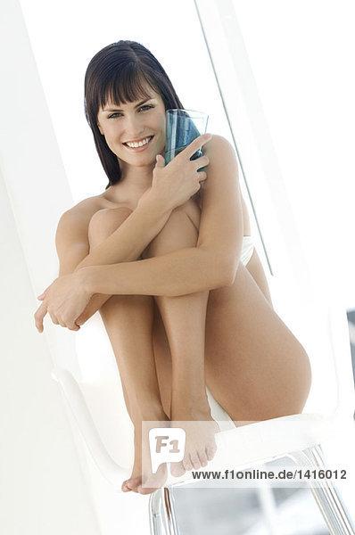Junge lächelnde Frau in Unterwäsche  die auf einem Stuhl sitzt und ein Glas Wasser hält.