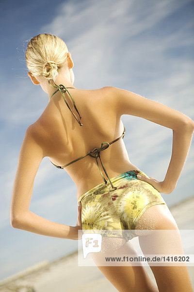 Junge Frau im Bikini am Strand stehend  Rückansicht