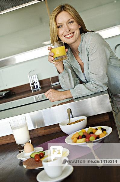 Lächelnde Frau mit Fruchtsaft