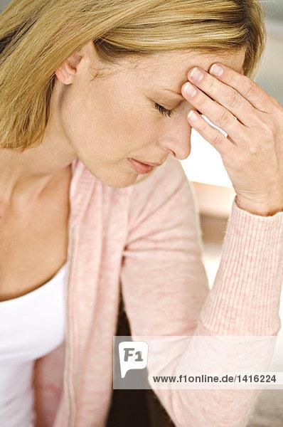 Frau mit Hand auf der Stirn  Augen geschlossen