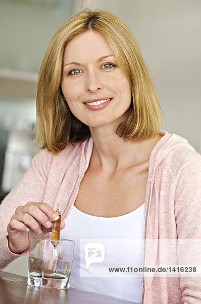 Frau entleert Ampulle im Glas