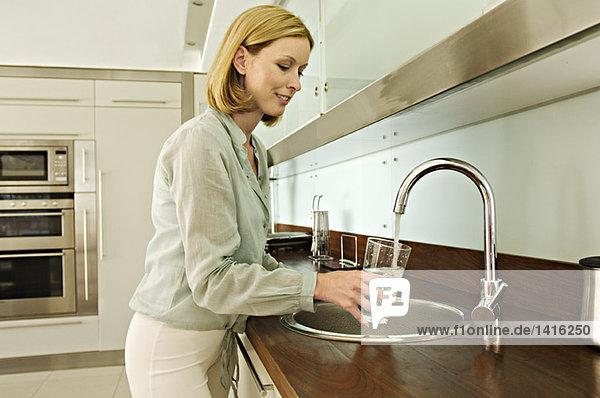Frau füllt Glas mit Leitungswasser