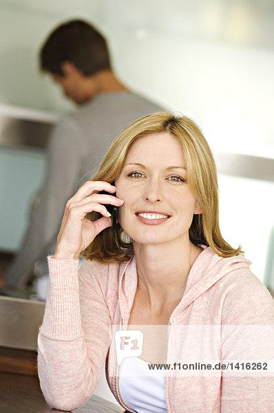 Frau mit Handy  Mann im Hintergrund