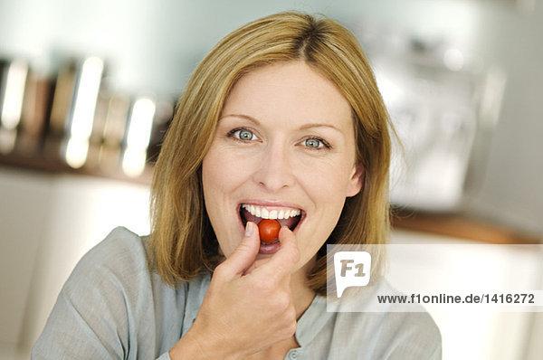 Porträt einer Frau beim Essen von Kirschtomaten