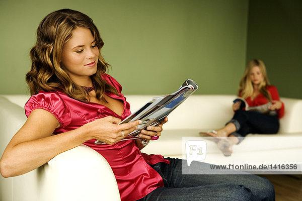 2 Frauen beim Lesen auf dem Sofa