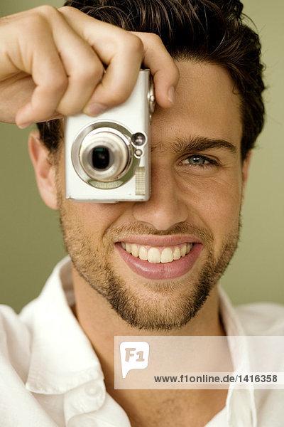 Porträt eines jungen Mannes beim Fotografieren