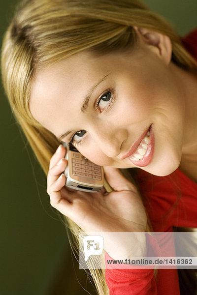 Porträt einer jungen lächelnden Frau  mit Handy